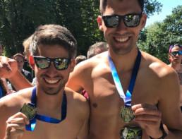 Zwei Läufer halten Medaille in die Kamera