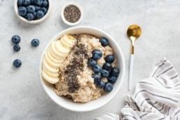 Blick von oben auf Porridge mit Blaubeeren und Bananen