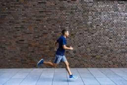 Läufer vor Mauer im Sprint