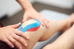 Kinesio-Tapes werden auf das Knie aufgeklebt