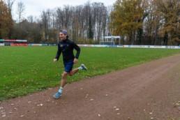 Sportler läuft Intervalle auf Aschebahn
